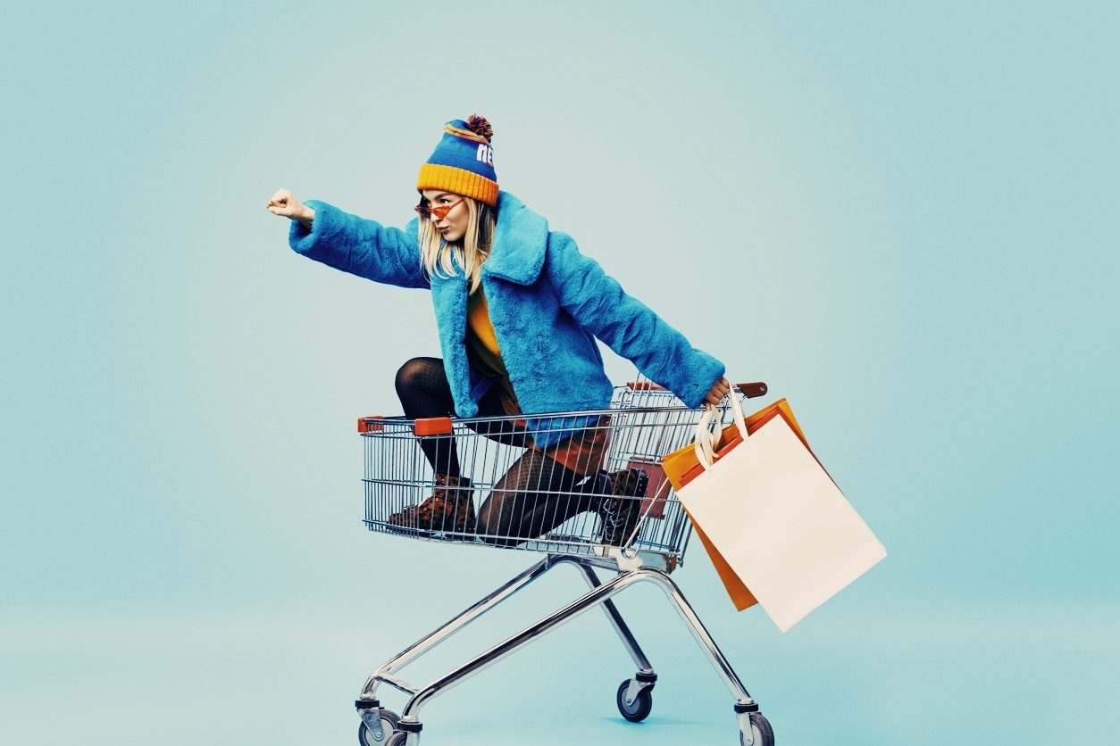 girl in shopping trolley with shopping bags